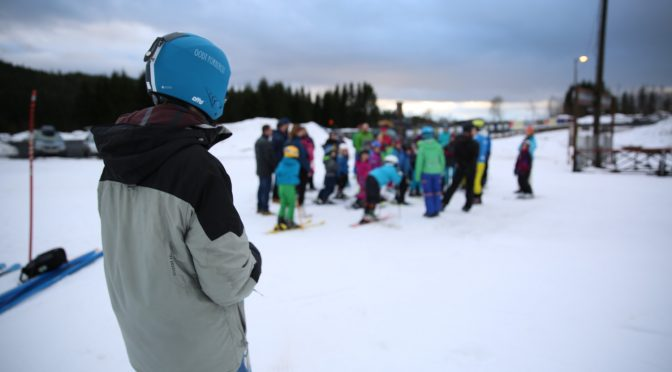 Student instructors give alpine skiing classes for children